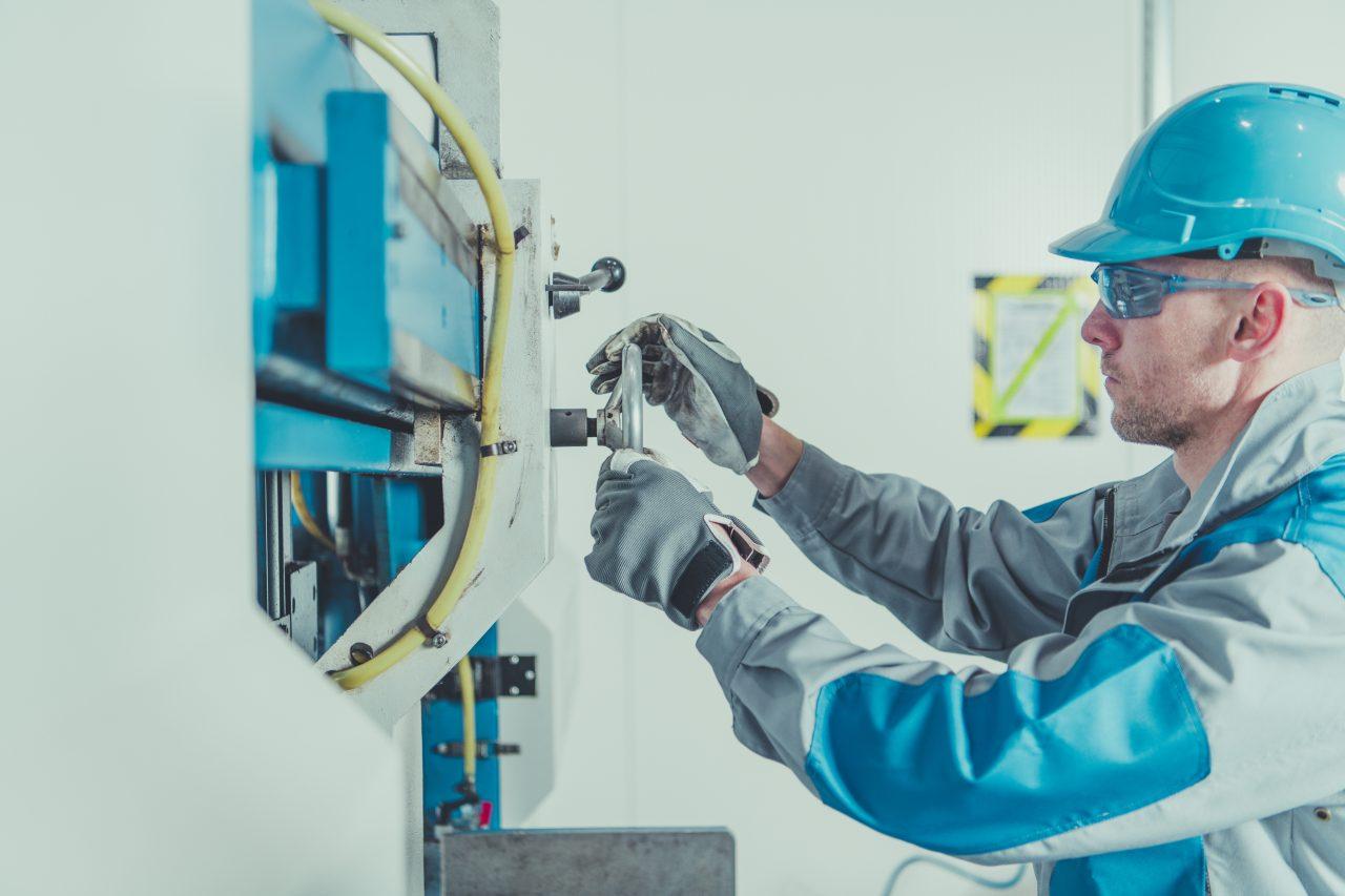 Metalworking Engineer Job. Caucasian Machine Operator Adjusting and Calibrating Metal Cutter.
